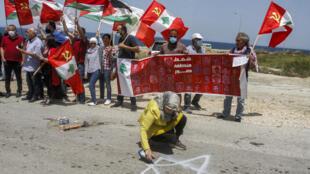 Un manifestante pinta la estrella de David en el suelo durante una protesta en contra de la reanudación del diálogo entre Líbano e Israel sobre la frontera marítima, el 4 de mayo de 2021 en Naqoura
