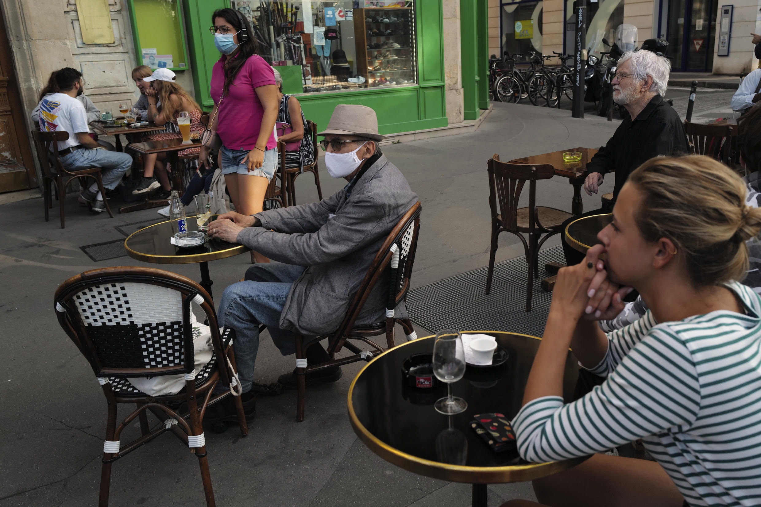 People, wearing a protective face mask as a precaution against the coronavirus, sit on the terrace of a cafe, in Paris, Thursday Sept. 10, 2020