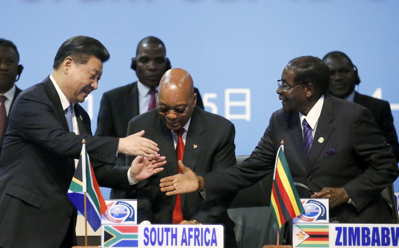 Le président chinois Xi Jinping serre les mains de son homologue zimbabwéen Robert Mugabe, sous l'oeil du président sud-africain Jacob Zuma, le 4 décembre 2015 à Johannesbourg.