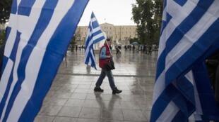 Homem passeia em frente ao Parlamento grego, neste sábado.