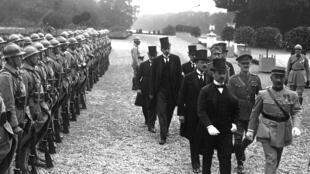 Cérémonie de signature du traité de Trianon: à l'avant en haut-de-forme Ágost Benárd, chef de la délégation hongroise, passant devant un piquet d'honneur à Versailles.