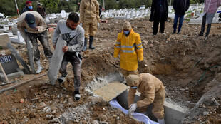 Tunis municipality employees bury the body of a Covid-19 victim at the Jellaz cemetery in the capital Tunis