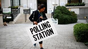 Un agent électoral installe des panneaux devant un bureau de vote de Londres, le 23 mai 2019.