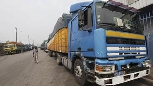 Lorries loaded with cocoa stand outside a warehouse at the port in Abidjan