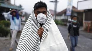 A man covers himself with a blanket as he stops to look at the Mount Sinabung