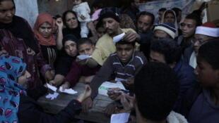 Pessoas tentam conseguir medicamentos em um bairro pobre da periferia do Cairo.