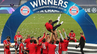 The Bayern Munich squad throw head coach Hansi Flick in the air after winning the Champions League final.