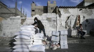Distribution alimentaire par des travailleurs de l'UNRWA au camp d'al-Shati, à Gaza, le 6 avril 2020.