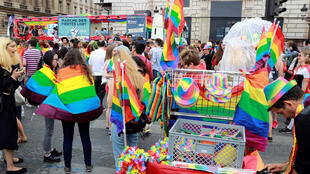Les gens arrivent avec des drapeaux arc-en-ciel pour participer à la parade de Fierté Homosexuelle, à Paris, le 24 juin 2017.