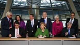 Le président du SPD Sigmar Gabriel (g.) et la chancelière allemande Angela Merkel(c), lors de la signature de l'accord sur la grande coalition, le 27 novembre 2013.