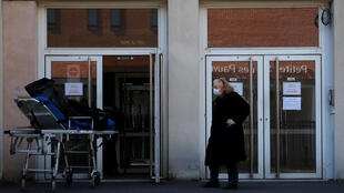 An elderly woman wearing a protective face mask stands next to a stretcher in front of the entrance of the Fondation Rothschild retirement home (Ehpad) in Paris where 16 residents have died and 81 have been infected with coronavirus disease (COVID-19) as the spread of the coronavirus disease (COVID-19) continues in France, March 25, 2020.  REUTERS/Gonzalo Fuentes