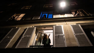 巴黎人在窗口鼓掌感谢支持奋斗在第一线的医护工作人员,2020年3月18