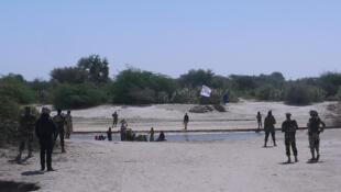 Soldados nigerianos enfrentam membros do Boko haram. Ao fundo, a bandeira do grupo terrorista.