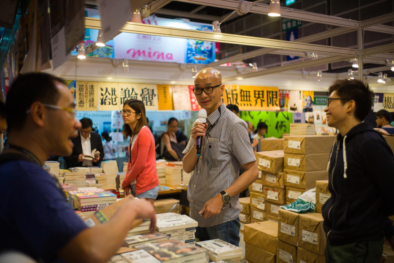2016年7月20日,香港书商彭志铭(中)在香港书展期间与顾客交流。