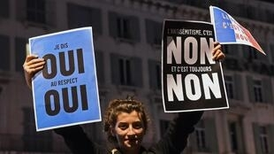 A young woman holds placards as she takes part with others in a rally against anti-semitism in Marseille on February 19, 2019.