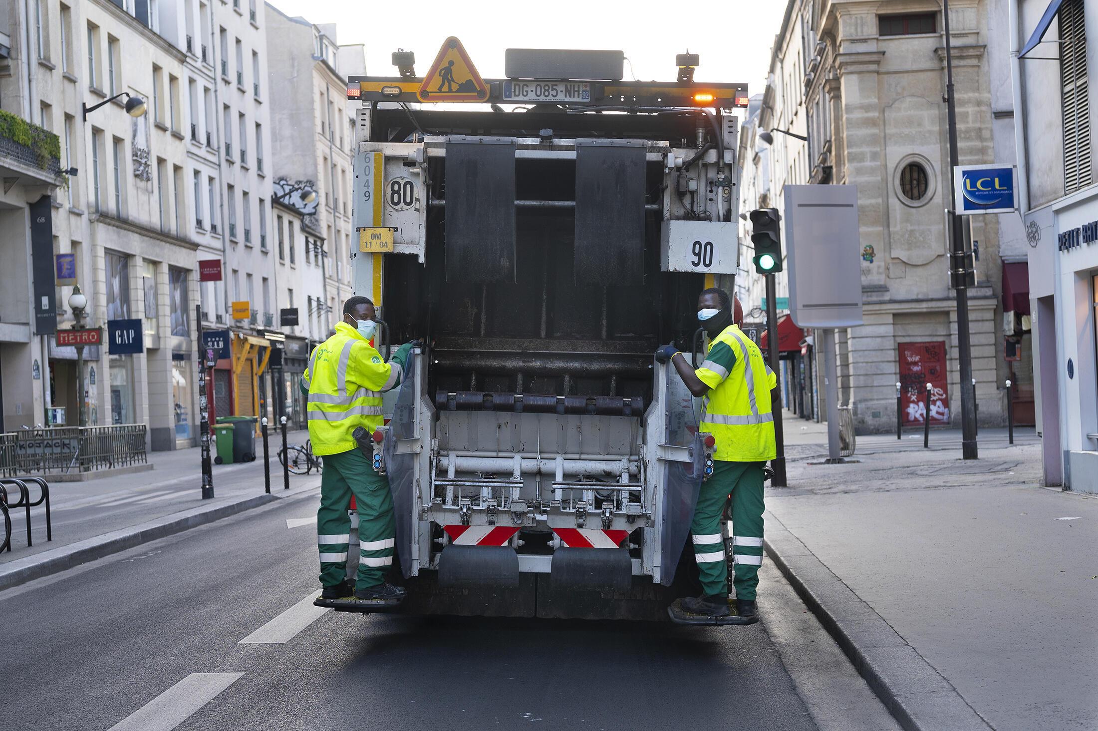Des éboueurs à Paris, rue du Faubourg Saint-Antoine.
