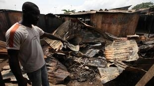 A man points to a burnt shop near Williamsville after a clash between Ivorian security forces and pro-Outtara fighters in Abidjan. 15 March 2011.