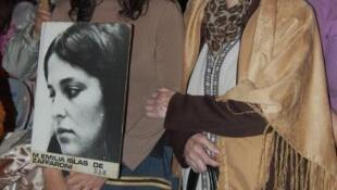 Mariana Zaffaroni, junto a su abuela y el retrato de su madre asesinada.