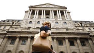 Una mujer pasa frente a la sede del Banco de Inglaterra, el 17 de junio de 2020 en el centro de Londres