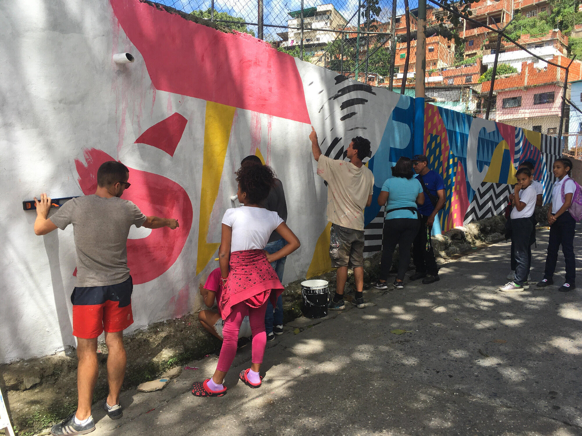 Seb Toussaint (à gauche) aidé par les jeunes du quartier à qui il donne des conseils. Sur cette fresque, en plein centre du quartier sur la place principale, c'est le mot «résilience» qui va être peint.
