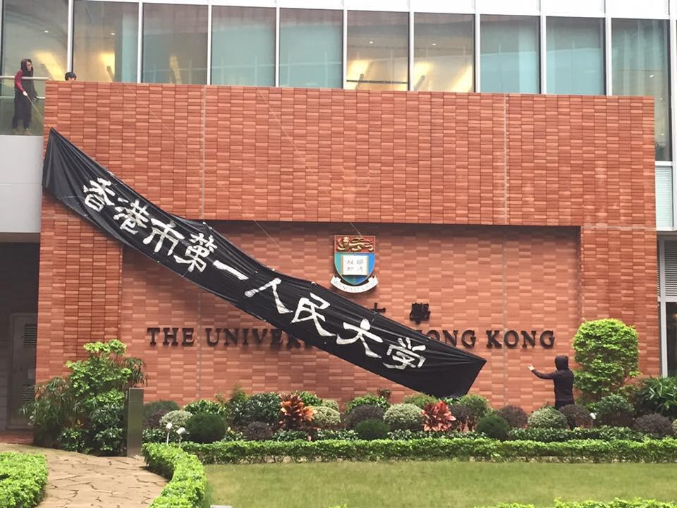 """港大罢课委员会成员现于百周年校园C出口写有""""香港大学""""的牆外,挂上""""香港市第一人民大学""""横幅。"""