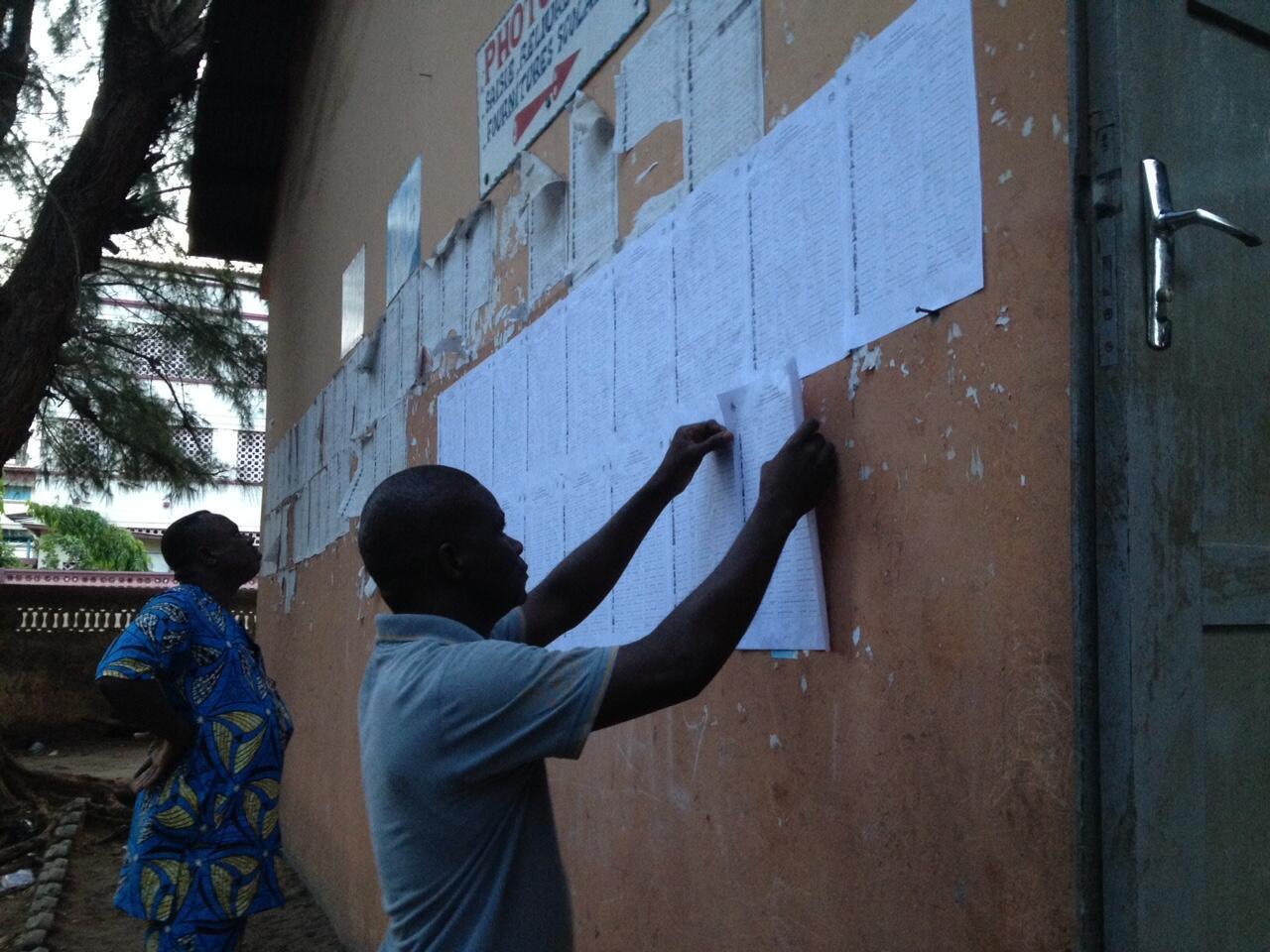 Au Bénin, les électeurs cherchent leur nom sur la liste affichée près de chaque bureau de vote pour les élections législatives, ici à Cotonou le 26 avril 2015.