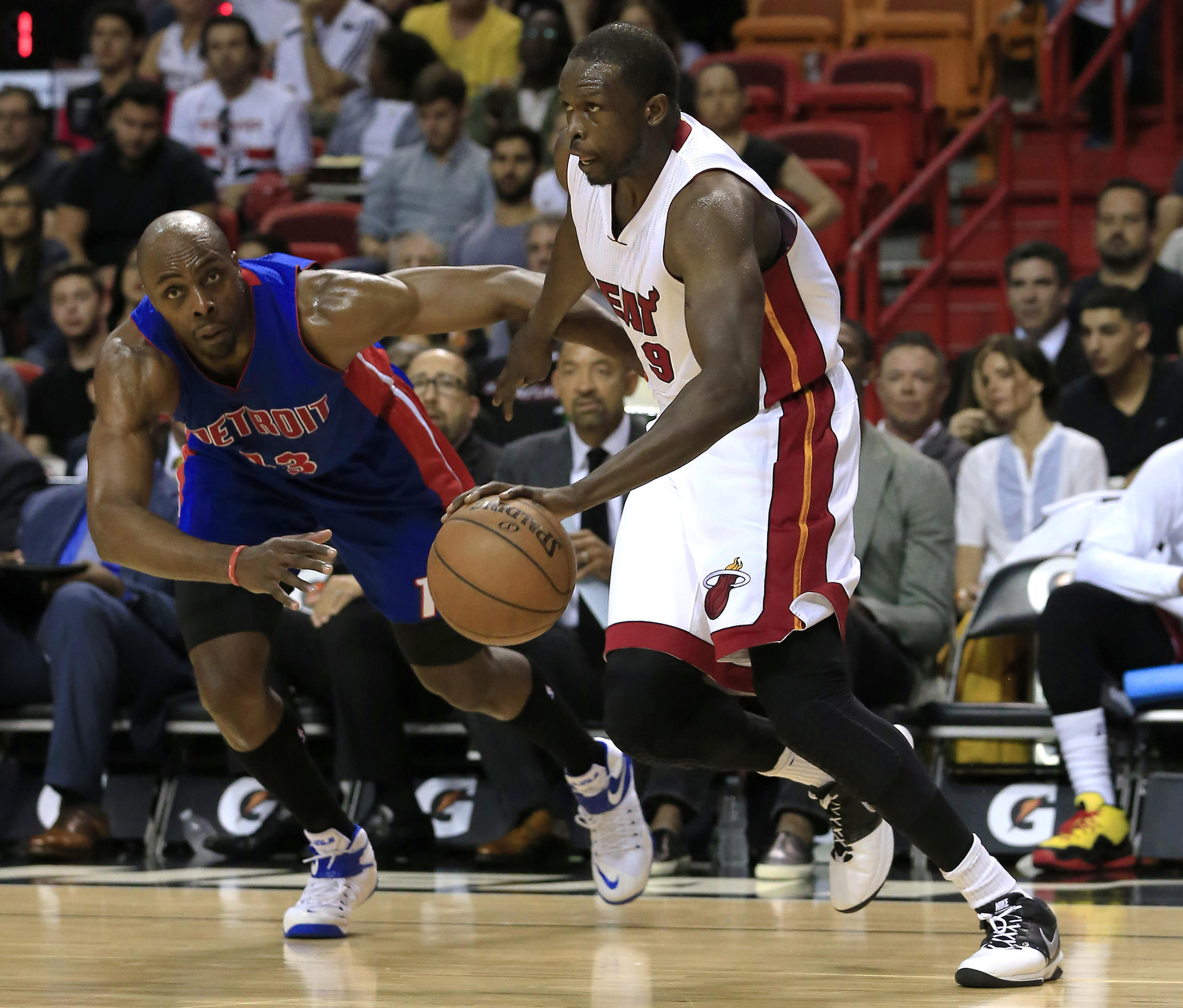 Miami Heat forward Luol Deng (right) dribbles the ball in the match against Detroit Pistons.