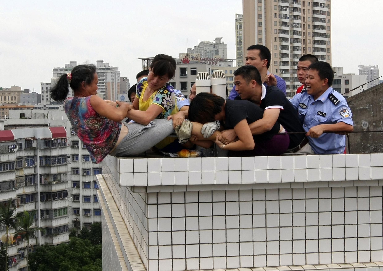 Les secours et des passants tentent d'empêcher le suicide d'une jeune Chinoise à Zhanjiang, le 14 août 2012.
