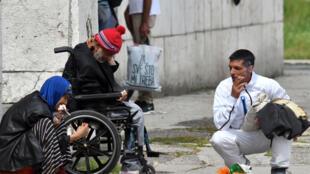 Un migrant handicapé âgé partage une cigarette avec d'autres alors qu'il se réfugie à l'extérieur de la gare de Sarajevo à Sarajevo le 23 juin 2018.