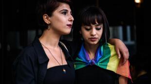 Duas mulheres observam a polícia dispersar a Parada Gay em Istambul.