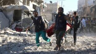 Des volontaires syriens transportent un blessé après des bombardements le 30 septembre 2016 sur la zone rebelle de Heluk à Alep.