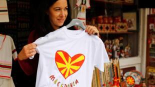 Una turista en una tienda de souvenirs con la bandera de Macedoniae en el viejo bazar de Skopie.