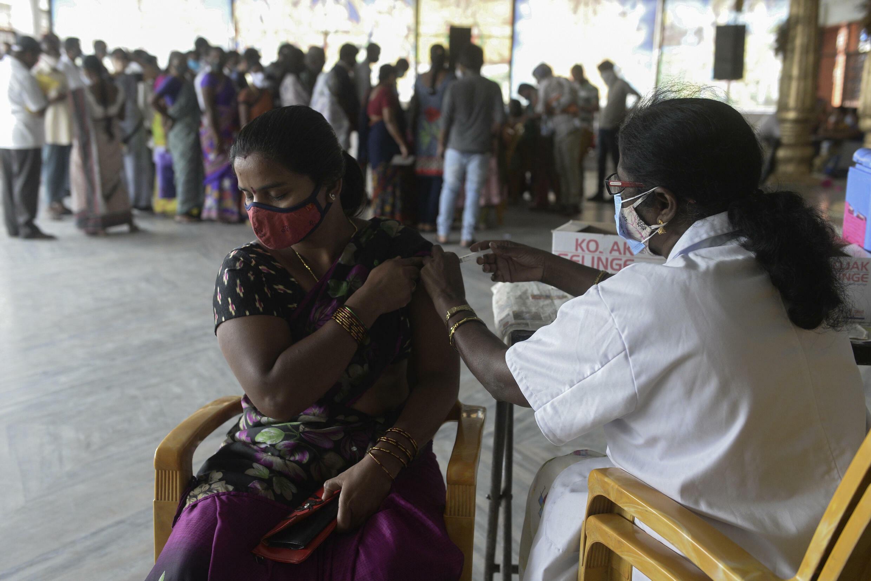 Una empleada del personal sanitario inyecta una dosis de la vacuna de Covishield contra el coronavirus a una mujer en un centro de vacunación instalado a las afueras de Hyderabad, el 15 de julio de 2021 en el centro-sur de la India