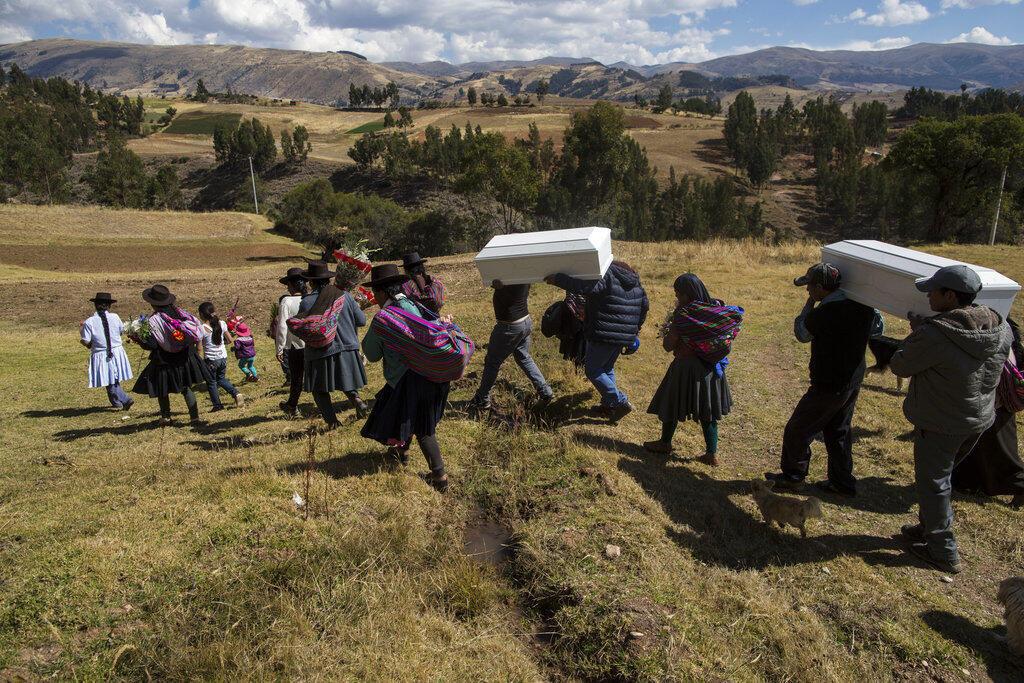 En esta foto del 15 de agosto de 2018, gente lleva los restos de personas asesinadas por la guerrilla de Sendero Luminoso en 1984, durante su entierro en Tantana, en la provincia peruana de Ayacucho. Los restos óseos de 14 personas fueron entregados recientemente a sus seres queridos en virtud de una nueva ley que las autoridades esperan acelere lo que ha sido durante mucho tiempo un proceso largo y engorroso para identificar a los muertos en el conflicto.