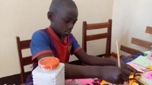 Un enfant recueilli par le centre de Bakanja de Lubumbashi pratique une activité manuelle.