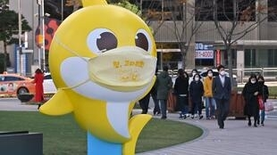"""People walk past a shark character from the children's song """"Baby Shark"""" at Seoul Plaza in Seoul on 3 November, 2020, a day after the song became the most-watched YouTube video with more than seven billion plays."""