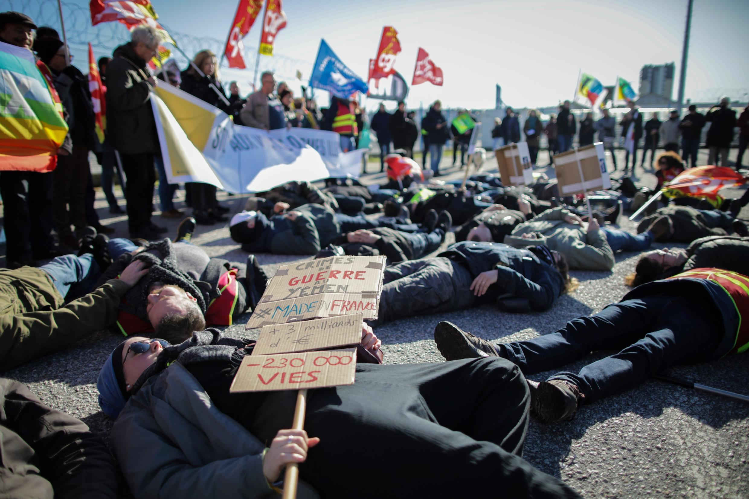 """Militants of several humanitarian associations including """"Amnesty International"""" lay on the ground at Cherbourg harbor, to prevent a Saudi ship accused of transporting weapons for the conflict in Yemen, from docking, February 6, 2020"""