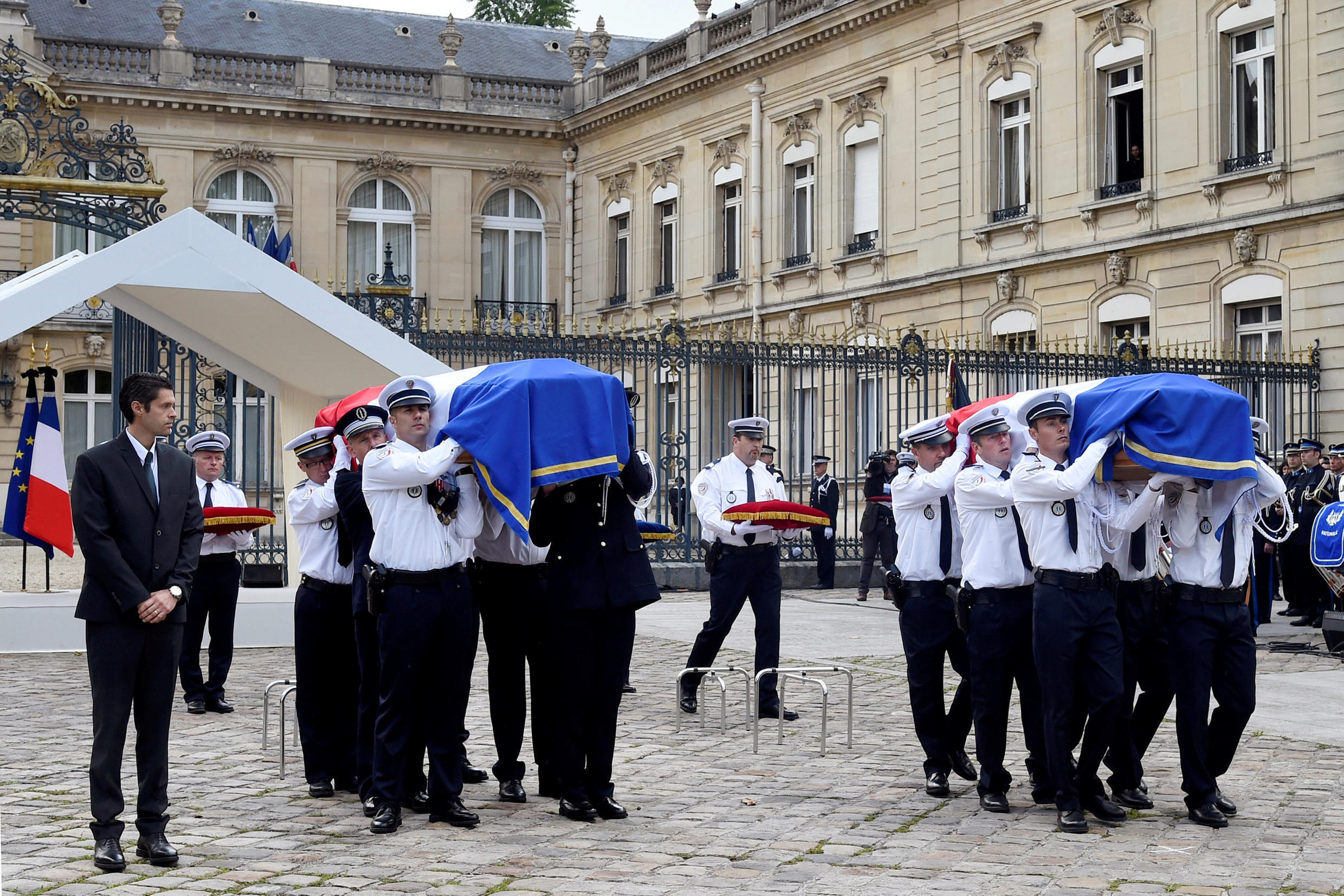 Police carry the flag-draped coffins honouring the police couple, French police commander Jean-Baptiste Salvaing and his companion, administrative agent Jessica Schneider, during a memorial ceremony in Versailles, near Paris, France, June 17, 2016.