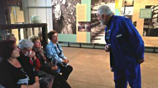 Dans la salle des pendus du Centre Historique Minier de Lewarde, Daniel, ancien mineur devenu guide, raconte au public son premier jour à la mine.
