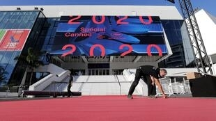"Workers install the red carpet in front of the main entrance of the Palais des Festivals before the opening ceremony of the ""Cannes 2020 Special"" event in Cannes on 27 October 2020."
