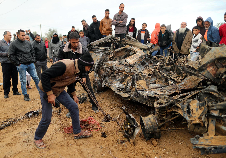 Palestinos revisan los restos de vehículos destrozados por el ataque aéreo de Israel.