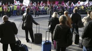 Passageiros observam manifestação de grevistas no aeroporto de Frankfurt, nesta terça-feira.