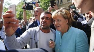 Angela Merkel pose pour une photo avec un réfugié du centre d'accueil de Spandau.