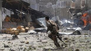 A Somali soldier runs near the scene of a deadly blast in Mogadishu 14 April 2013