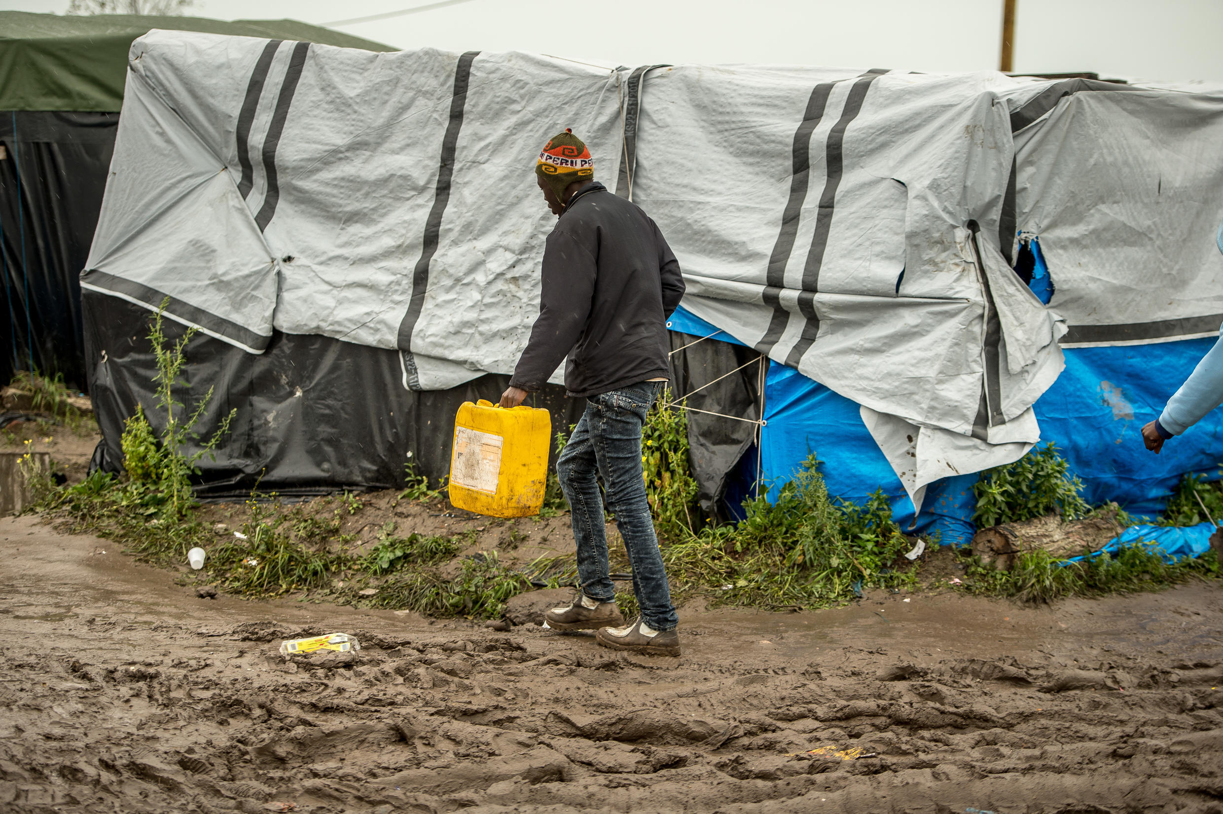 21 October 2015 - A man walks through the 'New Jungle' migrants camp in Calais, where thousands of people live, in the hope of crossing the Channel to Britain.