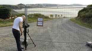 A cameraman shoot the closed entrance of the Saint-Maurice beach where most of dead wild boars were found.