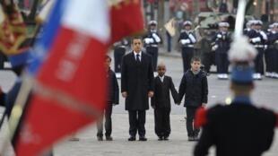No Arco do Triunfo, em Paris, Nicolas Sarkozy dá a mão a filhos de soldados mortos no Afeganistão.