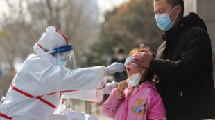Un sanitario recoge muestras de una niña para someterlas a una prueba de ácido nucleico para detectar posibles casos de coronavirus COVID-19 el 5 de marzo de 2020 en una zona residencial de Wuhan, en la provincia china de Hubei