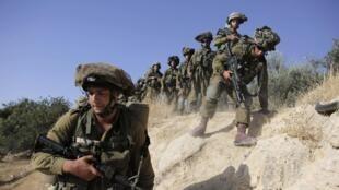 Soldados israelenses vasculham a Cisjordânia à procura de três estudantes sequestrados.