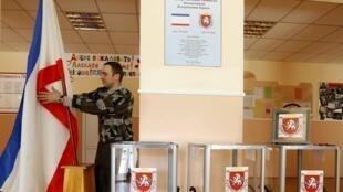 Agente municipal instala bandeira da Crimeia em seção eleitoral de Simferopol, 15 de março de 2014.